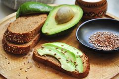 Toast with avocado on a wooden table with salt, bread and flax seeds on a wooden board. royalty free stock images