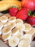 Toast with bananas and strawberries for breakfast. A healthy, clean whole food breakfast including wheat toast with peanut butter and bananas sliced on top, and Royalty Free Stock Photography
