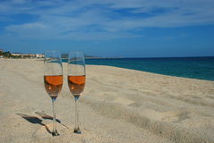 Toast at the beach. Two glasses with pink champagne at Costa Azul beach Los Cabos Mexico, a well known vacation destination stock image