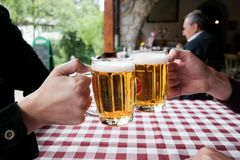 Toast with beer. Cheers with beer, young man drinking alcohole Royalty Free Stock Photography