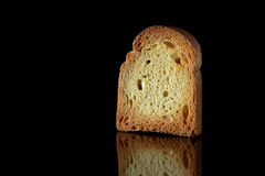 Toast on black. Close up of golden slice of toast on black background with reflection Stock Image