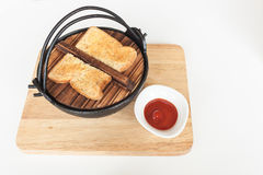 Toast on black iron bowl and tomato sauce on wood tray Royalty Free Stock Image