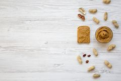 Toast, bowl of peanut butter and peanuts in shells on a white wooden background, top view. Copy space. stock images