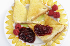 Toast bread with butter and raspberry jam on plate Stock Photography