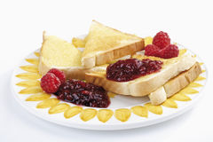 Toast bread with butter and raspberry jam on plate Stock Photos