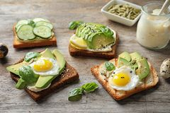 Toast bread with fried eggs, avocado. And cucumber slices on wooden table royalty free stock images