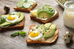 Toast bread with fried eggs, avocado. And cucumber slices on wooden table royalty free stock image