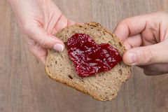 Toast bread with jam shape of hearts, vintage wooden table. Royalty Free Stock Photos