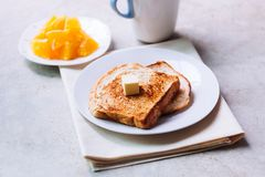 Toast bread on white plate. Toast bread on white plate with butter melting on and some orange fruit beside with ceramic glass Royalty Free Stock Images