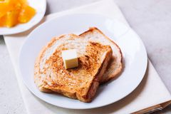 Toast bread on white plate. Toast bread on white plate with butter melting on and some orange fruit beside with ceramic glass Royalty Free Stock Image