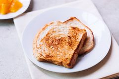Toast bread on white plate. Toast bread on white plate with some orange fruit beside with ceramic glass Stock Photos