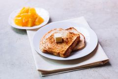 Toast bread on white plate. Toast bread on white plate with butter melting on and some orange fruit beside with ceramic glass Stock Photos