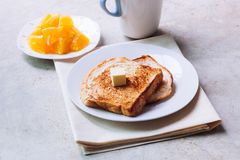 Toast bread on white plate. Toast bread on white plate with butter melting on and some orange fruit beside with ceramic glass Royalty Free Stock Photo