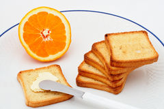 Toast with butter and half orange Royalty Free Stock Image