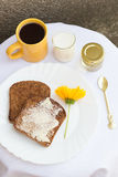 Toast with Butter, Honey, Coffee and Milk. Toast with Butter, a Yellow Flower, a Honey Jar, a Glass of Milk and a Cup of Coffee with a Golden Spoon Stock Photo