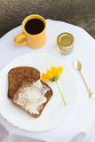 Toast with Butter, Honey and Coffee. Toast with Butter, a Yellow Flower, a Honey Jar and a Cup of Coffee with a Golden Spoon Stock Images