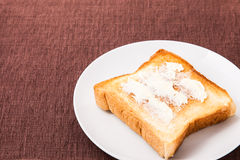 Toast and butter that is placed on a dish Royalty Free Stock Photography