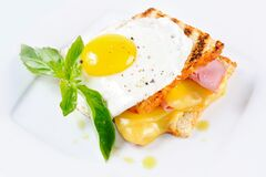 Toast with cheese and meat on top of scrambled eggs with herbs