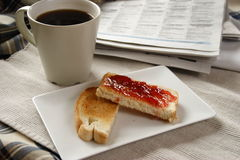 Toast_with_coffee. Toast with jam on a plate a cup of black coffee and newspaper in background Royalty Free Stock Photography