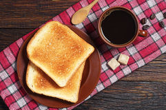Toast and coffee cup. Toast and cup of hot coffee on red tablecloth. Top view Stock Photo