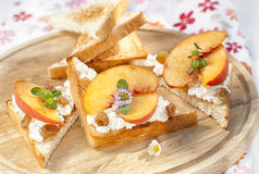 Toast with cottage cheese, raisins and fresh ripe peaches. Decorated with mint on the wooden surface Royalty Free Stock Photos