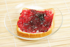 Toast with cowberry jam on mat Royalty Free Stock Photography