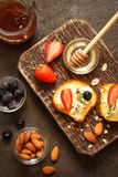 Toast with cream cheese, fresh strawberries, almond flakes, blue Royalty Free Stock Photos