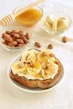 Toast with cream cheese, topped with banana, almonds and honey Royalty Free Stock Photos