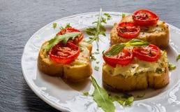 Toast (Crostini) mit Ricotta, Kirschtomaten und Arugula stockfoto