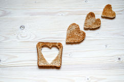 Toast with cut out a heart inside and three small hearts of white bread on a wooden surface. Royalty Free Stock Photos