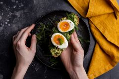 Toast with egg and avocado on bread in woman`s hands on black background royalty free stock photos