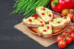 Toast with egg cream. Chopped chives, cherry tomatoes, red bell pepper on a black rustic wooden background selective focus royalty free stock photography
