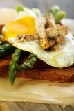 Toast with egg, green asparagus and turkey on the old board.. Stock Photography