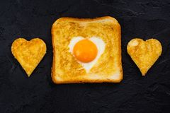 Toast with egg for Valentines day. Heart shaped fried egg baked in a toast. Tasty breakfast for Valentines day on black background. Space for text Royalty Free Stock Photos