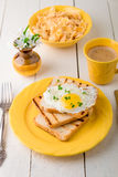 Toast with egg in yellow plate near vase with flower on white wooden background. Healthy breakfast. Stock Photography
