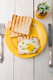 Toast with egg in yellow plate near vase with flower on white wooden background. Healthy breakfast. Top view. Royalty Free Stock Photos