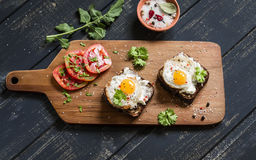 Toast with feta cheese and fried quail egg, fresh tomatoes on a dark wooden surface Stock Photography