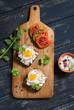 Toast with feta cheese and fried quail egg, fresh tomatoes on a dark wooden surface. A healthy Breakfast or snack Stock Images