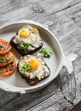 Toast with feta cheese and fried quail egg, fresh tomatoes on a light wooden surface Stock Photography