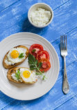 Toast with feta cheese and fried quail egg, fresh tomatoes on a  wooden surface. A healthy Breakfast or snack Stock Images