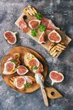 Toast with fresh figs, ham and cheese on a cutting Board,rustic background. Prosciutto with figs. Top view, flat lay. royalty free stock photos