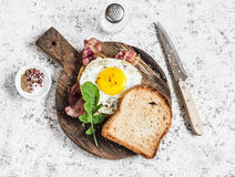 Toast with fried egg, bacon and arugula on the wooden cutting board. Delicious breakfast. Royalty Free Stock Photo
