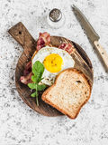 Toast with fried egg, bacon and arugula on the wooden cutting board. Delicious breakfast. On a light background Stock Images