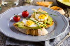 Toast with fried quail eggs and avocado Royalty Free Stock Photos