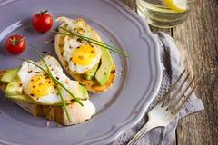 Toast with fried quail eggs and avocado Stock Photos
