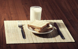 Toast with a glass of milk and knife on wooden background Royalty Free Stock Photography