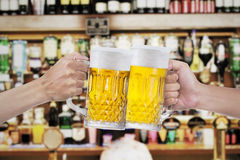 Toast with glasses of beer. Two human hands toast with glasses of beer at the bar Stock Photos