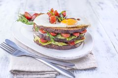 Toast from a grain bread with cheese and tomatoes and egg. Vegetarian food. on a white plate and blue dumbbells for fitness. Useful breakfast. Free space for Stock Photo