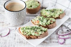 Toast with guacamole, seeds and herbs. A cup of coffee. Healyhy royalty free stock photo
