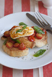 Toast with Halloumi. Toasted bread topped with roasted cherry tomatoes, Halloumi and basil Stock Photo
